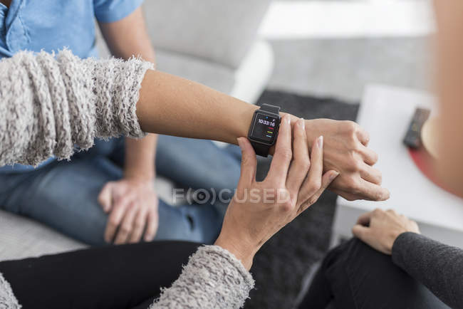 Woman's hand adjusting smartwatch at desk — Stock Photo