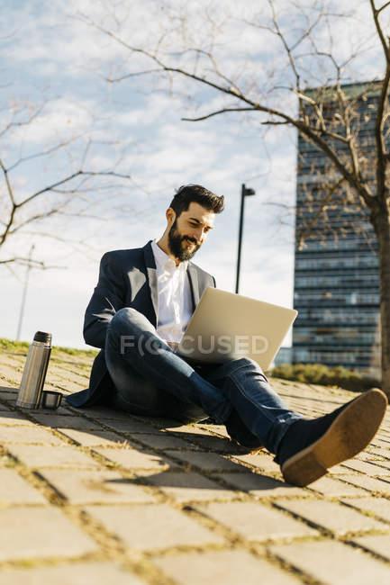 Uomo d'affari che utilizza laptop al di fuori dell'edificio per uffici — Foto stock
