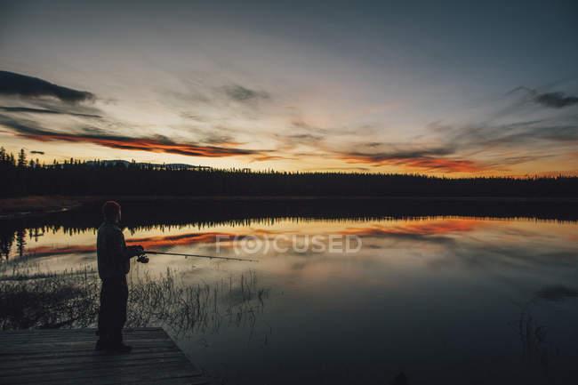 Канада, Британська Колумбія, людина ловить рибу на озері Духу на заході сонця. — стокове фото