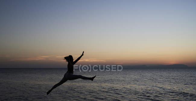 Jeune femme sautant à la mer au coucher du soleil — Photo de stock