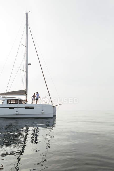 Coppia di partenza per un viaggio in barca a vela su un catamarano — Foto stock