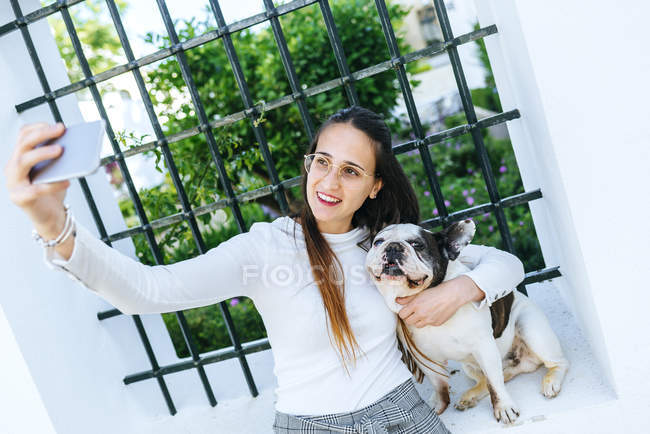Young woman using smartphone, taking a selfie with her dog — Stock Photo