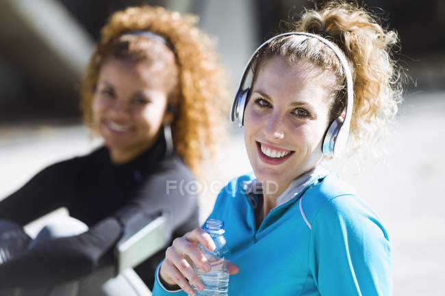 Portrait of two smiling sportive young women having a break — Stock Photo