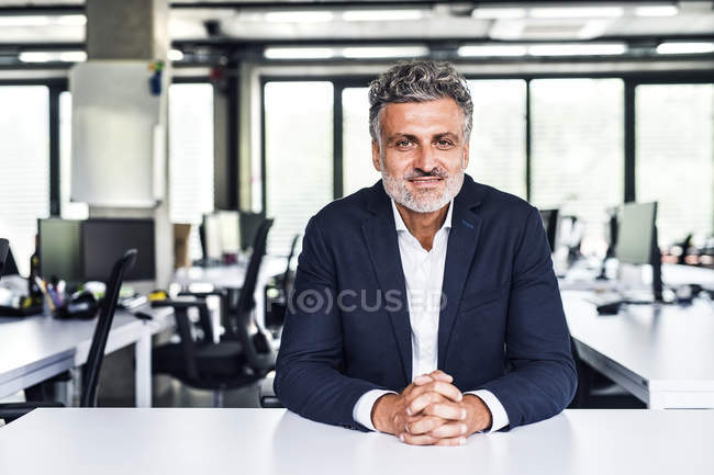 Portrait of smiling mature businessman sitting at desk in office — Stock Photo