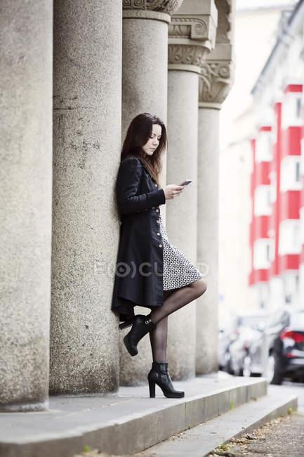Alemanha, Colônia, jovem elegante encostada à coluna e olhando para o telefone celular — Fotografia de Stock