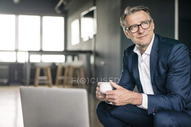 Улыбающийся взрослый бизнесмен с чашкой кофе, думающий — стоковое фото