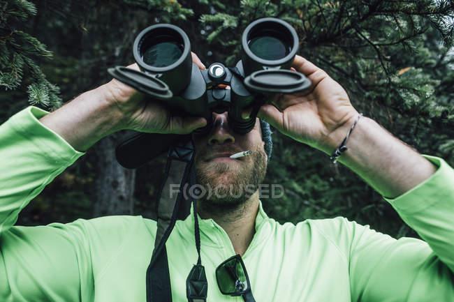 Hombre fumando un cigarrillo y mirando a través de los prismáticos en la naturaleza - foto de stock