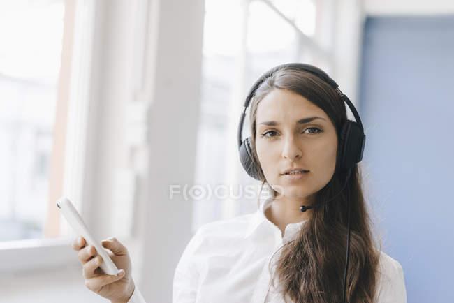 Jovem mulher usando smartphone, usando fone de ouvido — Fotografia de Stock