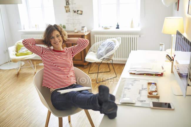 Porträt einer lächelnden reifen Frau, die es sich im heimischen Büro auf einem Sessel bequem macht — Stockfoto