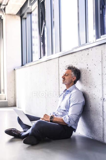 Empresário maduro com laptop sentado no chão e encostado à parede de concreto — Fotografia de Stock