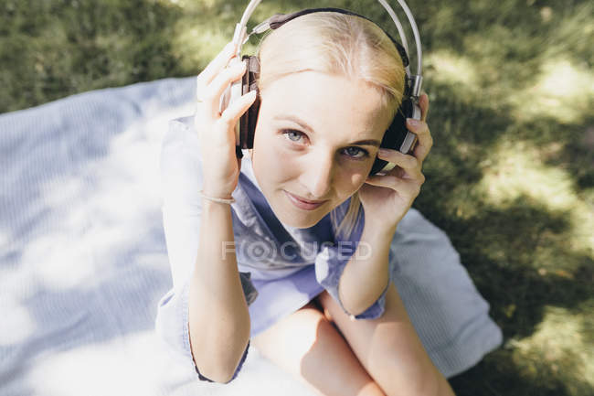 Portrait of smiling young woman sitting on blanket wearing headphones — Stock Photo