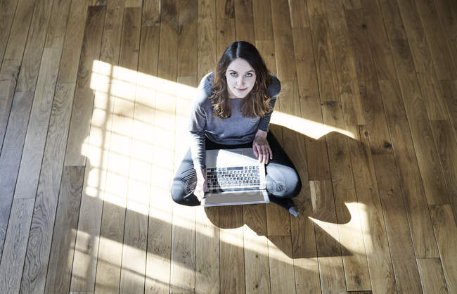 Portrait of young woman using laptop on wooden floor — Stock Photo