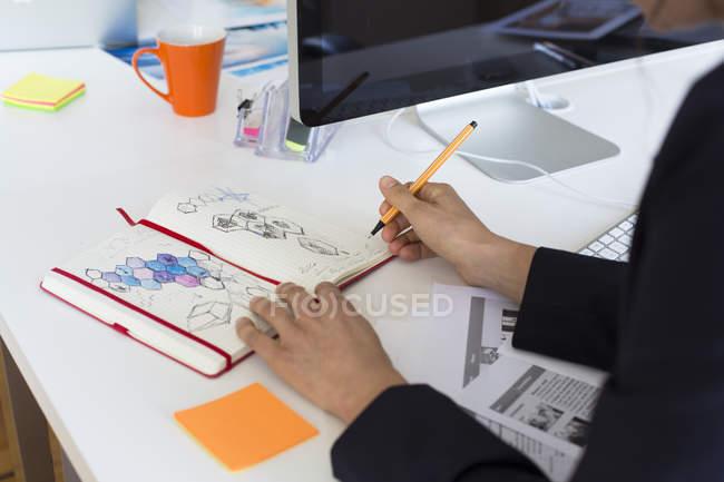 Donna che disegna nel quaderno alla scrivania in ufficio — Foto stock
