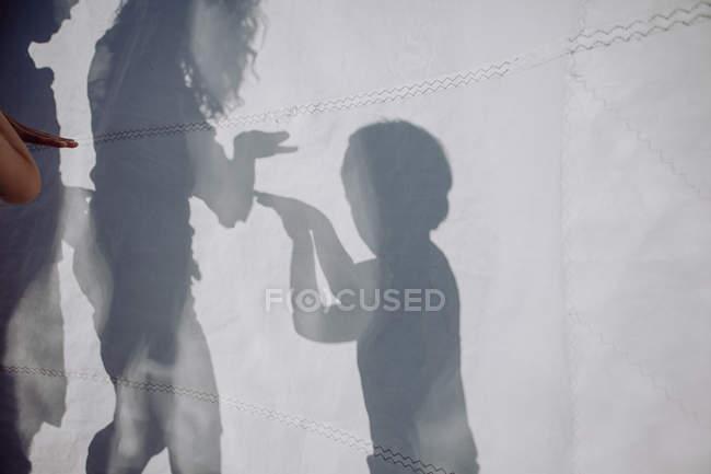 Familie spielt Schattenspiel hinter Segel — Stockfoto