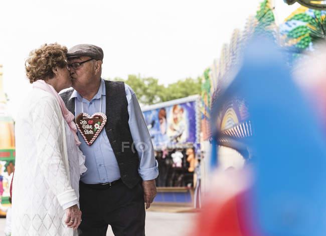 Coppia anziana con cuore di pan di zenzero baciare sulla fiera — Foto stock