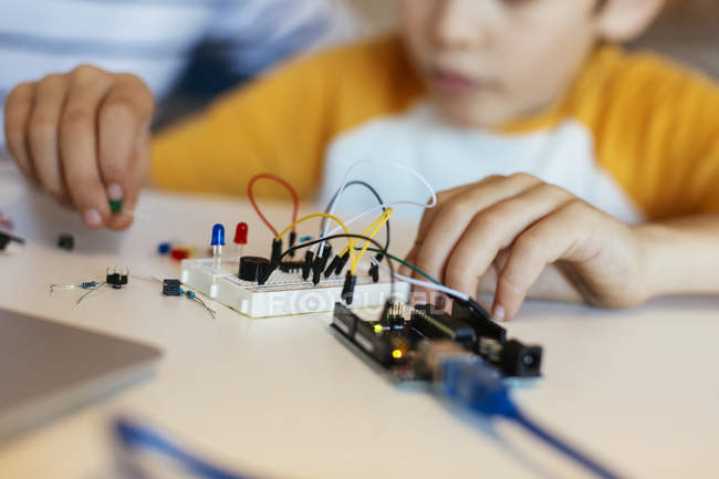 Close-up of little boy assembling electronic construction kit — Stock Photo