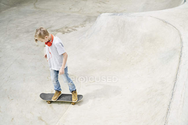 Junge mit Kopfhörern auf Skateboard, Skateboarding — Stockfoto