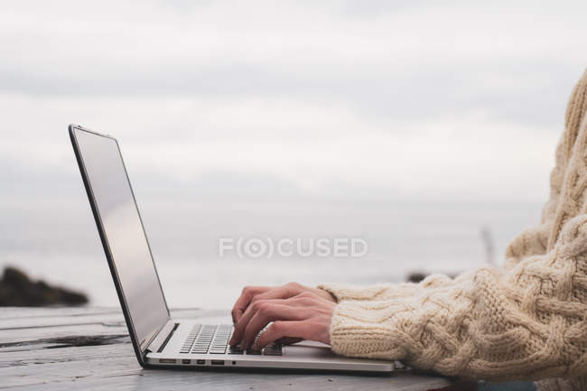 Islandia, mujer usando portátil en mesa de madera - foto de stock