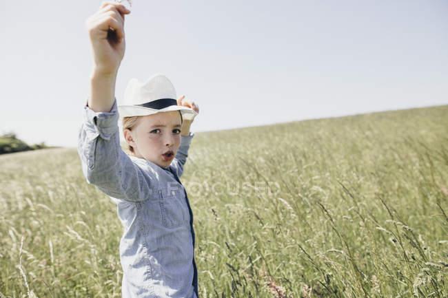 Boy wearing a hat dancing in field — Stock Photo