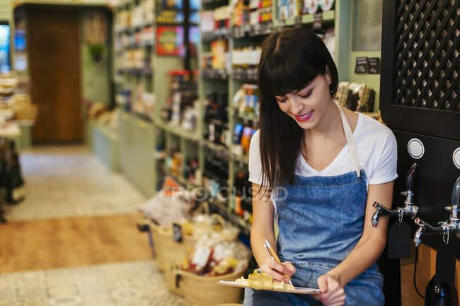 Усміхнена молода жінка в магазині беручи нотатки — стокове фото