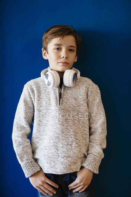 Portrait of little boy wearing headphones against blue wall — Stock Photo