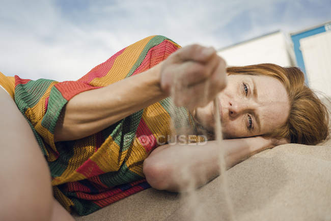 Redheaded woman lying on the beach, with sand trickling through her hand — Stock Photo