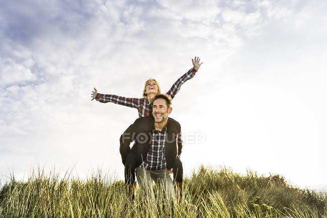 Glückliches verspieltes Paar in den Dünen — Stockfoto