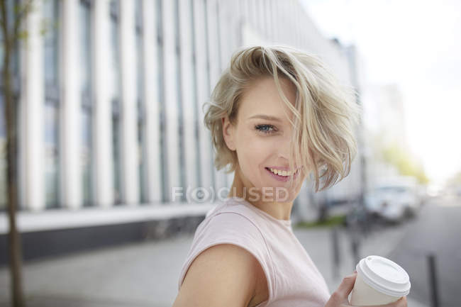 Porträt einer glücklichen blonden Frau mit Kaffee zum Mitnehmen in der Stadt — Stockfoto