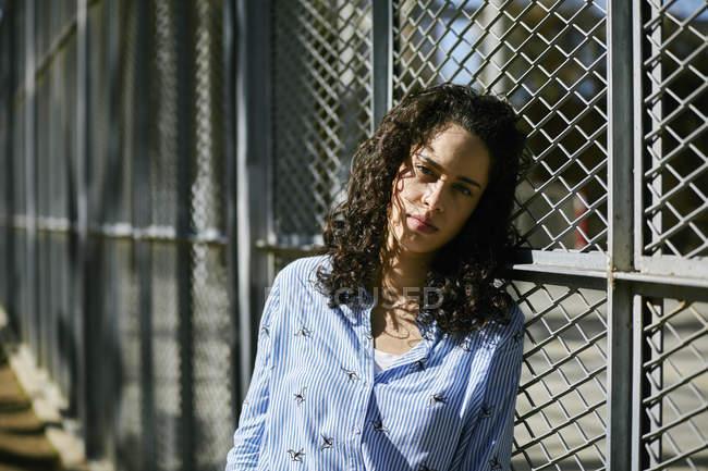 Ritratto di bella giovane donna appoggiata ad una recinzione — Foto stock