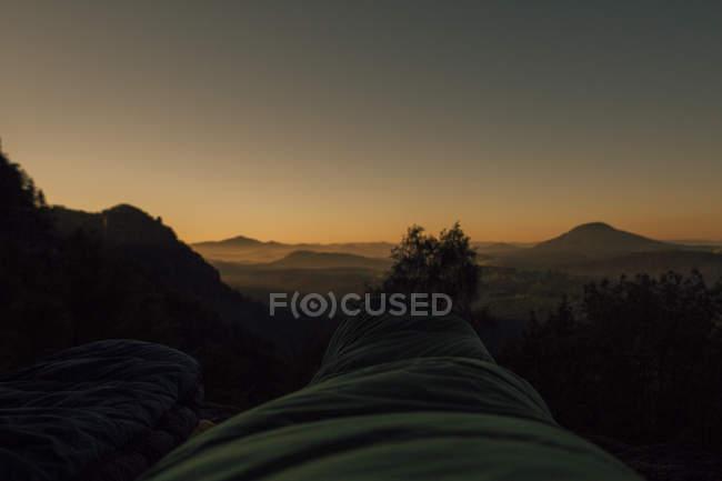 Czechia, Elbe Sandstone Mountains, Hiker lying in sleeping bag at sunrise — Stock Photo