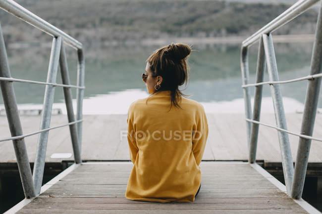 Vue arrière de la jeune femme assise sur la jetée — Photo de stock