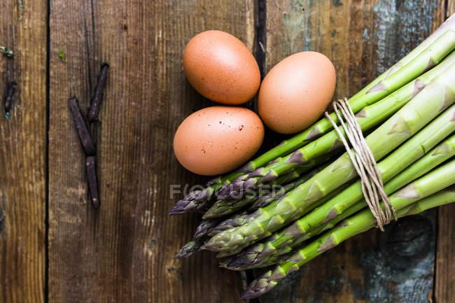Зеленая спаржа и коричневые яйца на лесистом фоне — стоковое фото