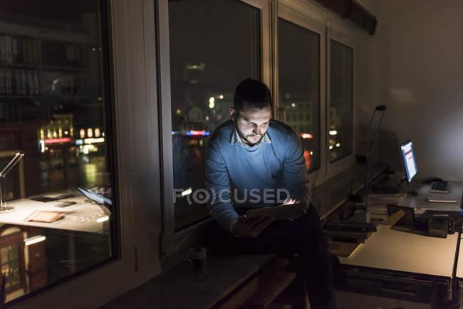 Homme d'affaires assis sur le rebord de la fenêtre dans le bureau la nuit en utilisant une tablette — Photo de stock