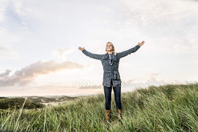 Glückliche Frau steht mit erhobenen Armen in den Dünen — Stockfoto