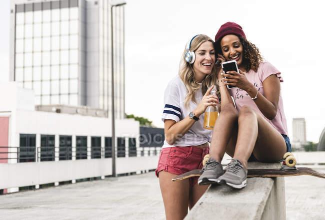 Beste Freunde mit Skateboard, Spaß zusammen, Musik hören — Stockfoto