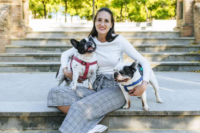 Ritratto di donna seduta nel parco con i suoi due cani — Foto stock