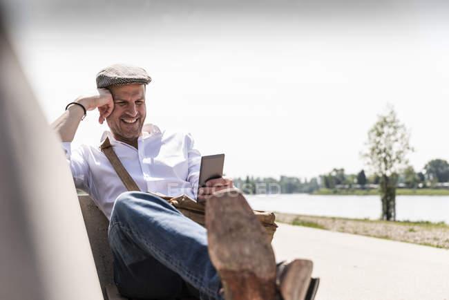 Зрелый мужчина с помощью смартфона на скамейке — стоковое фото