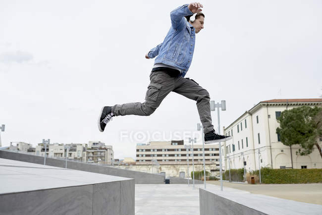 Junger Mann springt über Lücke zwischen Wänden, in der Luft — Stockfoto