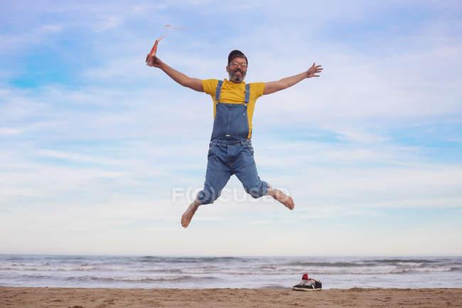 Ritratto di uomo felice in tunica che salta con soda in mano sulla spiaggia — Foto stock