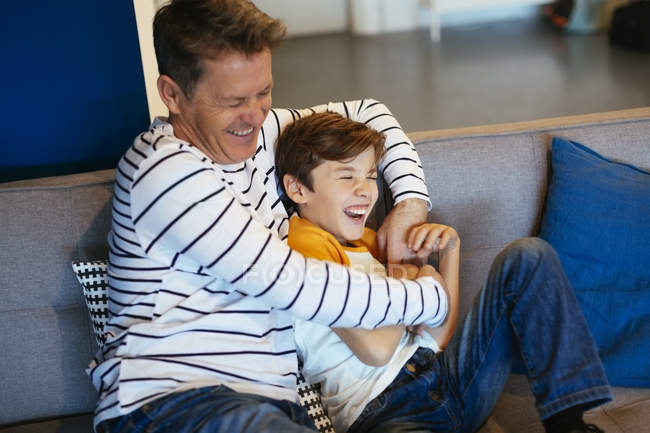 Carefree father and son having fun on couch at home — Stock Photo