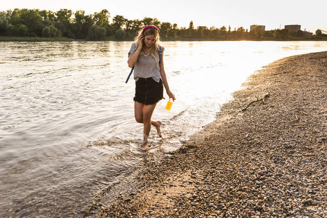 Jeune femme marchant pieds nus sur la rivière, écouteurs et smartphone — Photo de stock