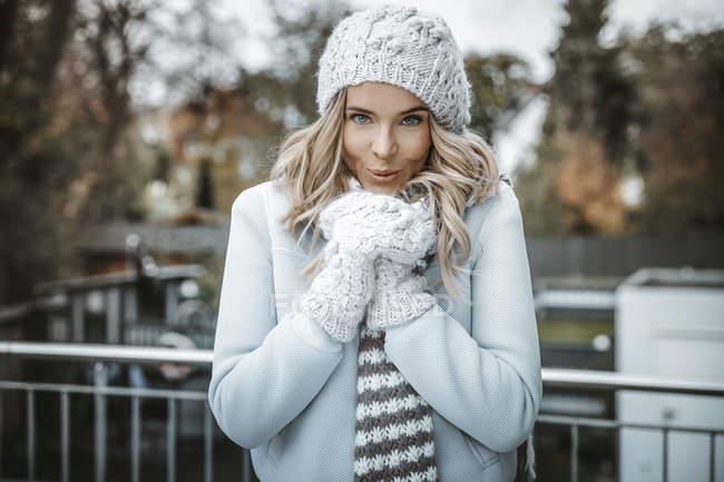 Retrato de una mujer sonriente con sombrero de lana, guantes y bufanda - foto de stock