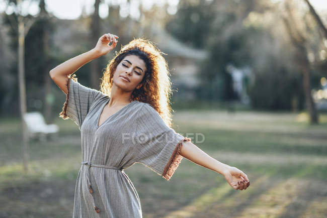 Portrait of fashionable young woman dancing in a park in the evening — Stock Photo