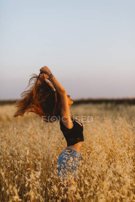 Young woman standing in grain field enjoying sunset — Stock Photo