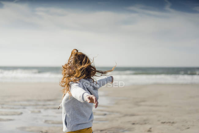 Redheaded woman relaxing on the beach, with arms outstretched — Stock Photo