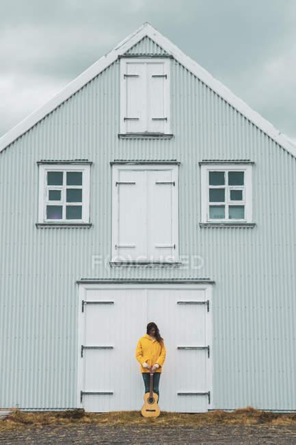 Islandia, mujer con guitarra de pie en casa - foto de stock