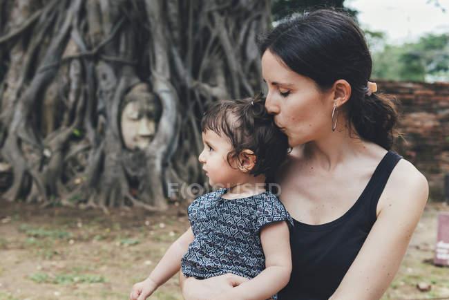 Mère embrassant sa fille à Wat Mahathat Ayutthaya avec la tête de bouddha dans les racines des arbres en arrière-plan — Photo de stock