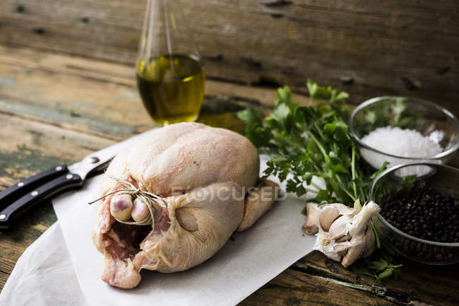 Uncooked chicken with parsil and garlic, olive oil, pepper and salt — Stock Photo