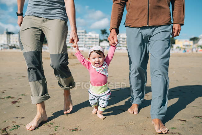 France, La Baule, portrait of happy baby girl walking on the beach with father and grandfather — Stock Photo