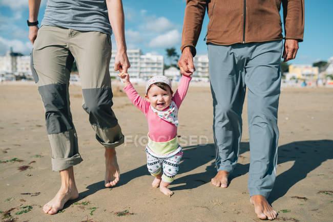 France, La Baule, portrait d'une heureuse petite fille marchant sur la plage avec père et grand-père — Photo de stock